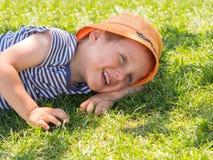 Le petit garçon se trouve sur une pelouse verte photo stock