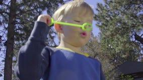 Le petit garçon souffle des bulles utilisant la baguette magique banque de vidéos