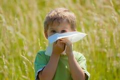 Le petit garçon souffle son nez Photos libres de droits