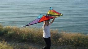 Le petit garçon supporte un cerf-volant multicolore au-dessus de sa tête vol d'imagination de jeu de concept des rêves clips vidéos