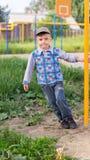 Le petit garçon sur une cour de jeu Image stock