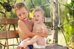 Le petit garçon tient sur des mains sa soeur de bébé Image stock