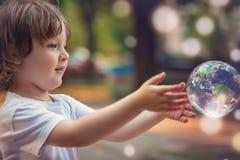 Le petit garçon tient une bulle de savon Photo libre de droits