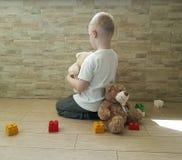 Le petit garçon triste avec l'ours de nounours reposant le port frustré remet la tristesse déprimé sur le plancher photographie stock libre de droits