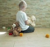 Le petit garçon triste avec le port se reposant d'ami d'ours de nounours remet la tristesse déprimé sur le plancher Photographie stock libre de droits