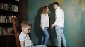 Le petit garçon triste est les parents de divorce de écoute combattent banque de vidéos