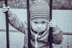 Le petit garçon triste regarde par un trellis Photo stock