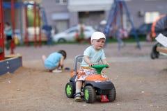 Le petit garçon conduit le jouet ATV Images stock