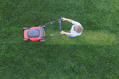 Le petit garçon coupe une herbe utilisant la tondeuse à gazon Image libre de droits
