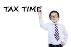 Le petit garçon écrit le temps d'impôts Image libre de droits