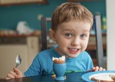 Le petit garçon heureux de trois ans mange un oeuf Image stock