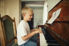Le petit garçon joue le piano Photographie stock libre de droits
