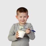 Le petit garçon mange du yaourt sur le gris Image libre de droits