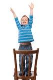 Le petit garçon soulève ses bras vers le haut Photo libre de droits