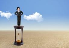 Le petit homme d'affaires se tient sur un sablier Image stock