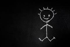 Le petit homme sur un tableau noir Photographie stock