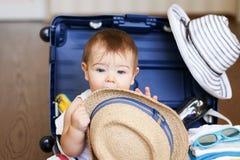 Le petit intérieur mignon de bébé garçon a emballé la valise avec le chapeau de paille dans des ses mains images stock