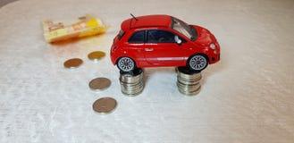 Le petit jouet rouge d'abarth de Fiat 500 se tient sur quatre colonnes des pièces de monnaie israéliennes d'un shekel photographie stock