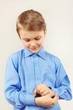 Le petit monsieur mignon a attaché les boutons sur la chemise lumineuse de douille Photo libre de droits