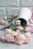Le petit oeillet rose tendre fleurit dans le vase à émail sur le béton gris avec l'espace de copie, verti Image stock