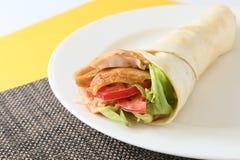 Le petit pain d'enveloppe de chiche-kebab avec les tomates et la laitue sur le plateau blanc image stock