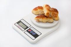 Le petit pain de grand-mamans roule sur l'échelle numérique de cuisine Images stock