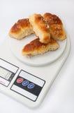 Le petit pain de grand-mamans roule sur l'échelle numérique de cuisine Images libres de droits