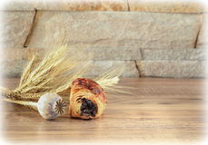Le petit pain doux avec le pavot se trouve sur une table en bois avec une tête et des épillets de pavot Photo stock