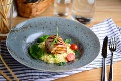 Le petit pain juteux de poulet avec le risotto, les tomates-cerises et la verdure d'un plat a servi à un dîner dans un restaurant photos libres de droits