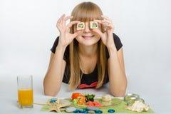Le petit pain mis de jeune fille vos yeux et avec le sourire regarde dans le cadre Photos libres de droits