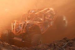 Le petit pain orange a mis en cage la voiture dans la pirogue avec la poussière rouge suspendue en air Photographie stock