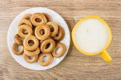 Le petit pain sonne dans le plat et la tasse blancs de lait Photos stock