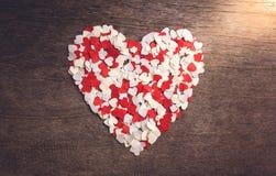 Le petit papier en forme de coeur a arrangé un grand coeur Photographie stock