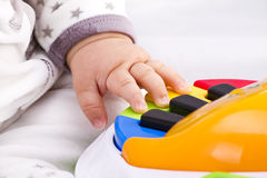 Le petit pianiste de main de chéri joue sur un jouet coloré Photographie stock