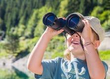 Le petit randonneur observe le panorama avec le télescope Images stock