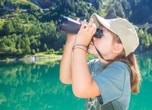 Le petit randonneur observe le panorama avec le télescope Photo libre de droits