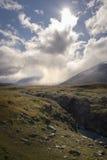Le petit randonneur seul se tenant dans l'énorme nuage et la lumière du soleil a couvert la région sauvage d'automne Photographie stock