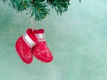 Le petit rouge deux a senti des bottes sur la branche de Noël artificiel t photos stock