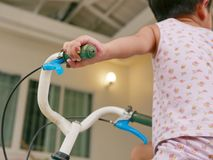 Le petit ` s de bébé remet tenir des guidons apprenant à monter une bicyclette photographie stock