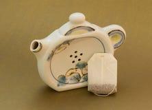 Le petit sachet à thé avec la théière a formé le support de sachet à thé image stock
