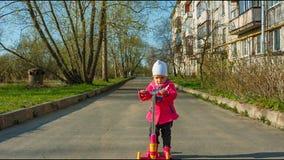 Le petit scooter mignon d'équitation de fille d'enfant en bas âge dans la ville, enfants folâtrent automne, dans le manteau banque de vidéos