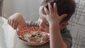 Le petit seul bébé mignon mange du gruau avec une cuillère d'un plat, le concept de la consommation saine banque de vidéos