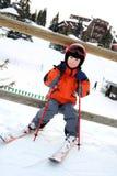 Le petit skieur s'assied sur la barrière en bois Photographie stock