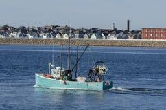 Le petit titre de bateau de pêche professionnelle vers des buses aboient images libres de droits