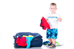 Le petit touriste rassemble des choses dans une valise pour la course Images stock