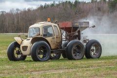 Le petit tracteur léger fait l'engrais sur le champ photo stock