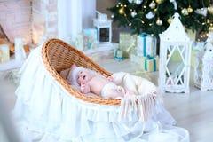 Le petit un bébé se situe dans le berceau dans le studio de blanc de Noël Images libres de droits