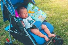 Le petit vieux bébé garçon asiatique de six mois mignon s'asseyent sur le carriag de poussette photo stock