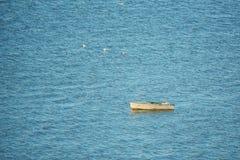 Le petit vieux bateau de pêche flotte sur l'eau photos stock