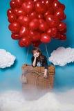 Le petit vol mignon de fille sur le coeur rouge monte en ballon le jour de valentines Images stock